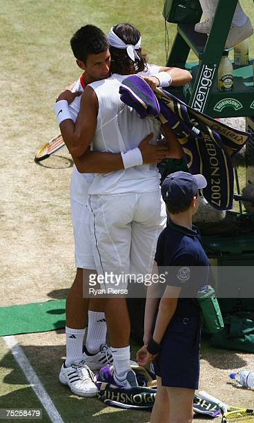 Novak Djokovic of Serbia embraces Rafael Nadal of Spain as he retires from the match due to injury during the Men's Singles semifinal match against...