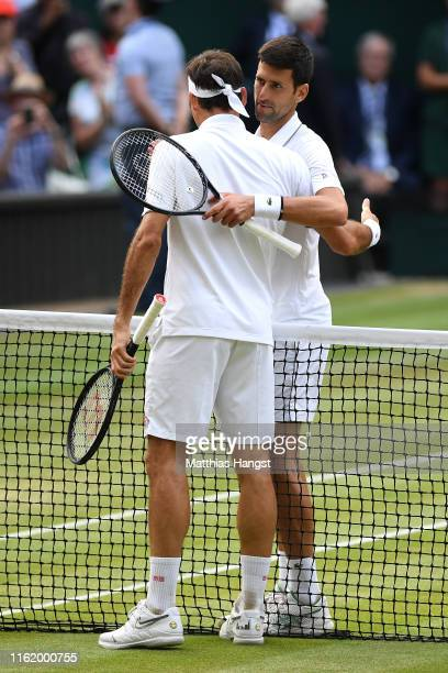 Novak Djokovic of Serbia embraces Roger Federer of Switzerland at the net following victory in his Men's Singles final during Day thirteen of The...