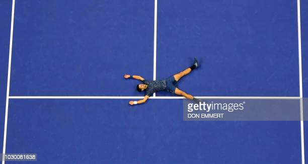 TOPSHOT Novak Djokovic of Serbia falls to the court in celebration after his victory over Juan Martin del Potro of Argentina during their 2018 US...