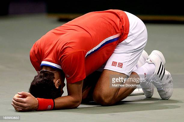 Novak Djokovic of Serbia falls to the court in pain after injuring his ankle in the third game of the first set in the fourth rubber against Sam...