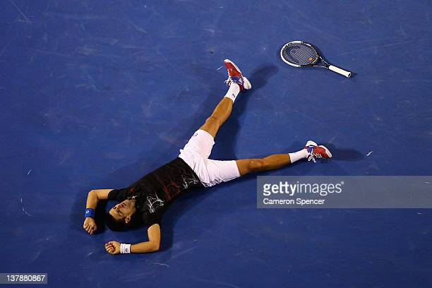 Novak Djokovic of Serbia falls to the floor exhausted after a 31 shot rally in his men's final match against Rafael Nadal of Spain during day...