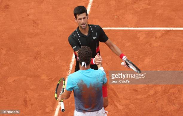 Novak Djokovic of Serbia greets Marco Cecchinato of Italy after losing to him during Day 10 of the 2018 French Open at Roland Garros stadium on June...