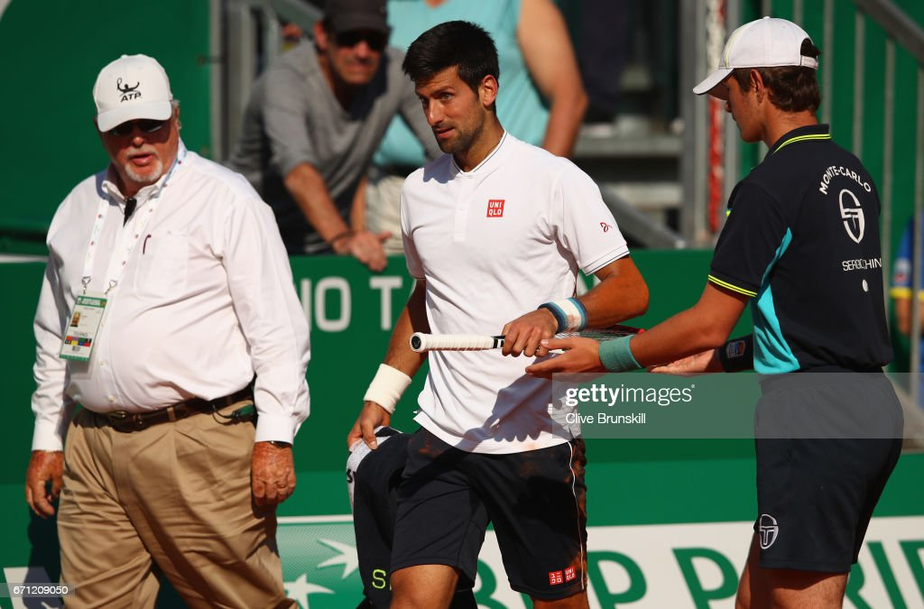 Novak Djokovic of Serbia has his racket handed to him by a ball boy after falling over against David Goffin of Belgium in their quarter final round match on day six of the Monte Carlo Rolex Masters at Monte-Carlo Sporting Club on April 21, 2017 in Monte-Carlo, Monaco.