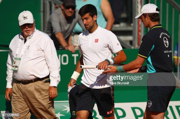 Novak Djokovic of Serbia has his racket handed to him by a ball boy after falling over against David Goffin of Belgium in their quarter final round...