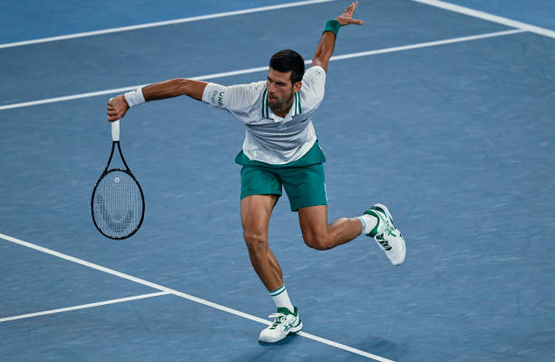 Novak Djokovic of Serbia hits a backhand against Aslan Karatsev of Russia in the men's semi-finals during day 11 of the 2021 Australian Open at...