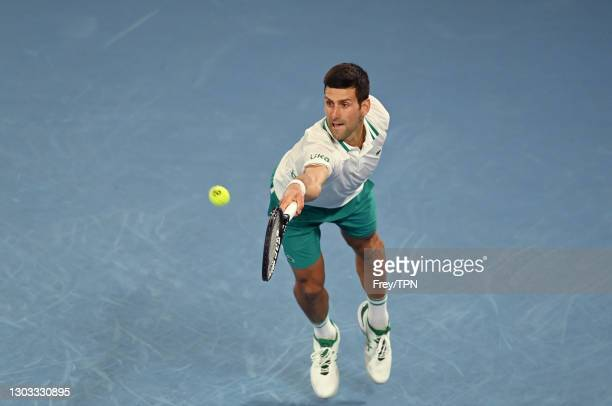 Novak Djokovic of Serbia hits a backhand against Daniil Medvedev of Russia in the men's singles final during day 14 of the 2021 Australian Open at...