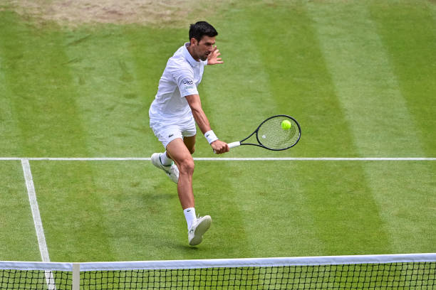 Novak Djokovic of Serbia hits a backhand against Marton Fucsovics of Hungary in the quarter finals of the gentlemen's singles during Day Nine of The...
