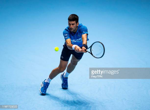 Novak Djokovic of Serbia hits a backhand against Roger Federer of Switzerland during Day Five of the Nitto ATP World Tour Finals at the O2 Arena on...
