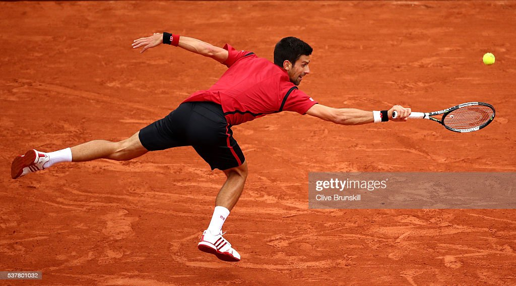 Novak Djokovic of Serbia hits a backhand during the Men's Singles semi final match against Dominic Thiem of Austria on day thirteen of the 2016 French Open at Roland Garros on June 3, 2016 in Paris, France.