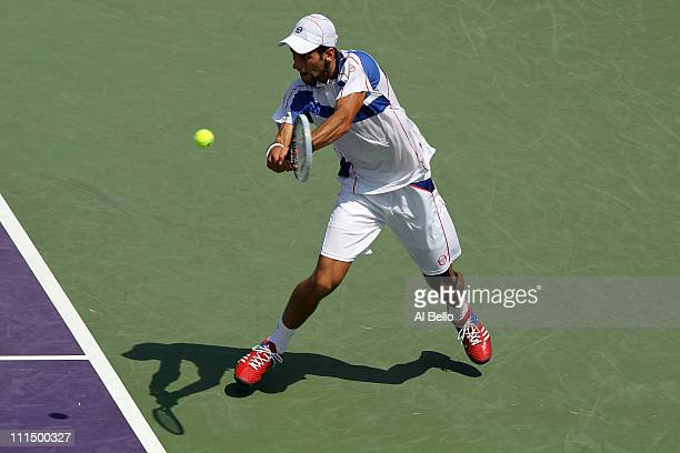 Novak Djokovic of Serbia hits a backhand return against Rafael Nadal of Spain during the men's singles championship at the Sony Ericsson Open at...