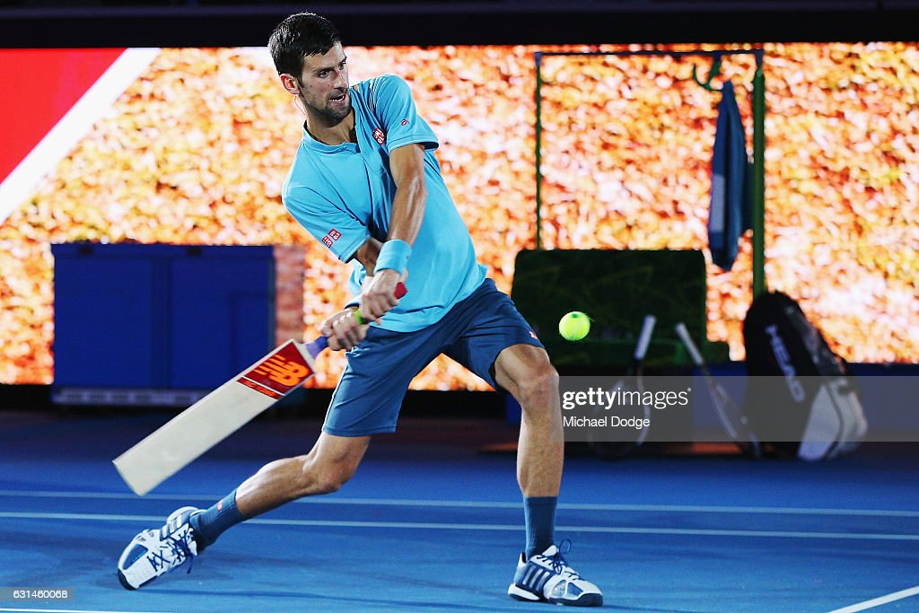 Novak Djokovic of Serbia hits a ball bowled by Australian cricket legend Shane Warne with a cricket bat during 'A Night with Novak' at Margaret Court Arena on January 11, 2017 in Melbourne, Australia.