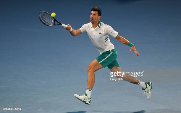 Novak Djokovic of Serbia hits a forehand against Daniil Medvedev of Russia in the men's singles final during day 14 of the 2021 Australian Open at...