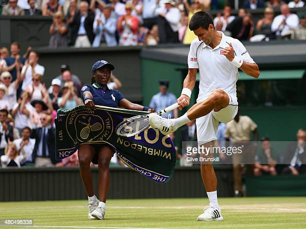 Novak Djokovic of Serbia hits his racket against his trainer in frustration after losing the second set in the Final Of The Gentlemen's Singles...