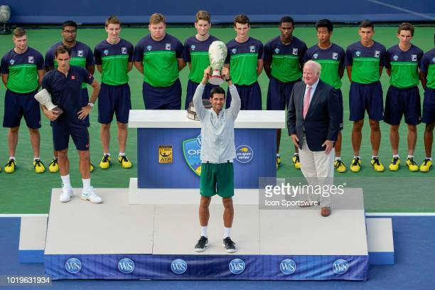 Novak Djokovic of Serbia hoists the trophy after defeating Roger Federer of Switzerland in the Western Southern Open singles final at the Lindner...
