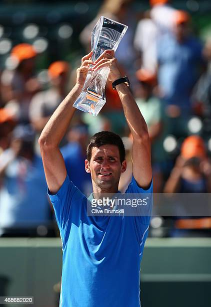 Novak Djokovic of Serbia holds aloft the Butch Buchholz trophy after his three set victory against Andy Murray of Great Britain in the mens final...