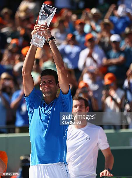 Novak Djokovic of Serbia holds aloft the Butch Bucholz trophy after his three set victory against Andy Murray of Great Britain in the mens final...
