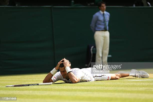 Novak Djokovic of Serbia holds his head in his hands and smiles after falling on the grass playing a forehand during the Gentlemen's Singles...