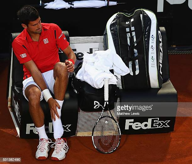Novak Djokovic of Serbia holds his left foot as he waits for treatment during his match against Kei Nishikori of Japan during day seven of The...