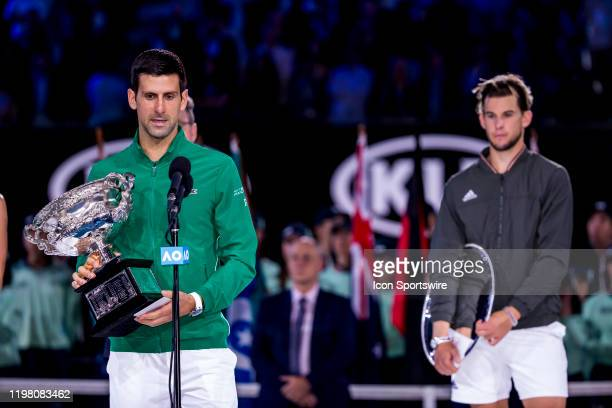 Novak Djokovic of Serbia holds his trophy speaking to the crowd while Dominic Thiem of Austria waits in the background after winning the finals of...