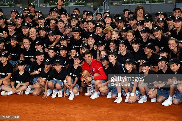 Novak Djokovic of Serbia holds his winners trophy as he poses for a photograph with the tournament ball boys and girls after his three set victory...