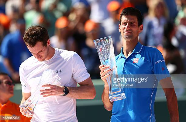 Novak Djokovic of Serbia holds the Butch Buchholz trophy after his three set victory against Andy Murray of Great Britain in the mens final during...