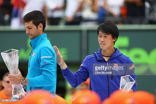 Novak Djokovic of Serbia holds the Butch Buchholz trophy after his straight sets victory against Kei Nishikori of Japan in the mens final during the...