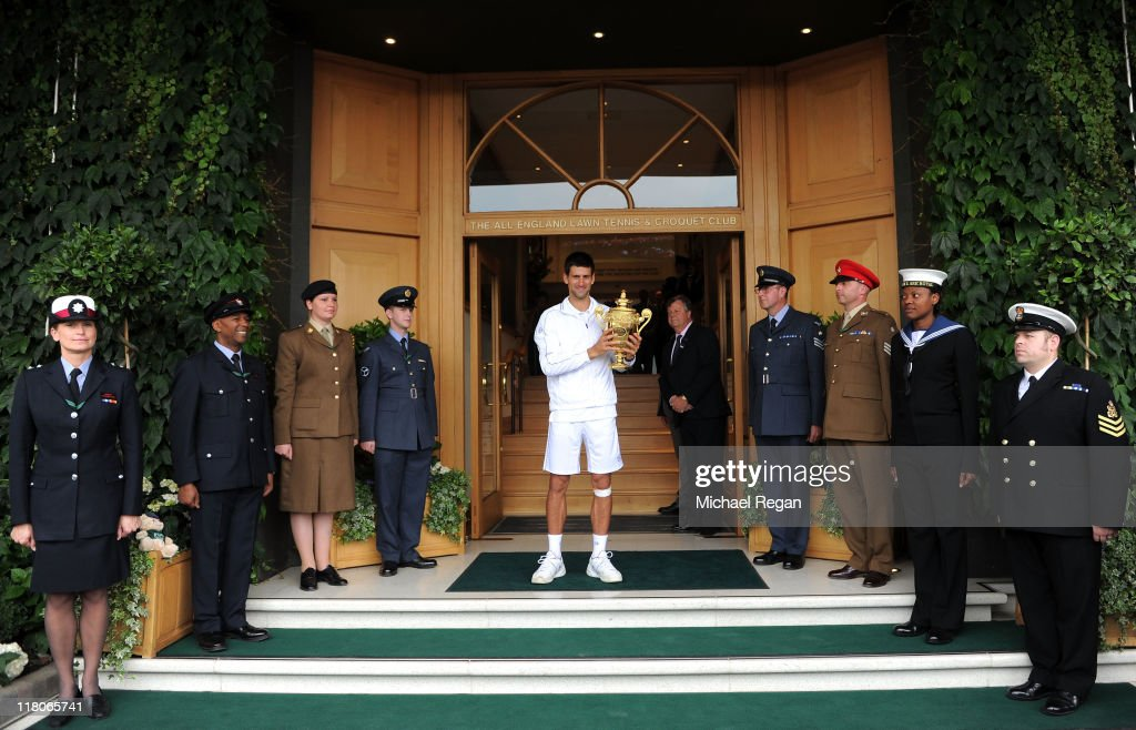 Novak Djokovic of Serbia holds the championship trophy outside the members entrance after winning his final round Gentlemen's match against Rafael Nadal of Spain on Day Thirteen of the Wimbledon Lawn Tennis Championships at the All England Lawn Tennis and Croquet Club on July 3, 2011 in London, England.