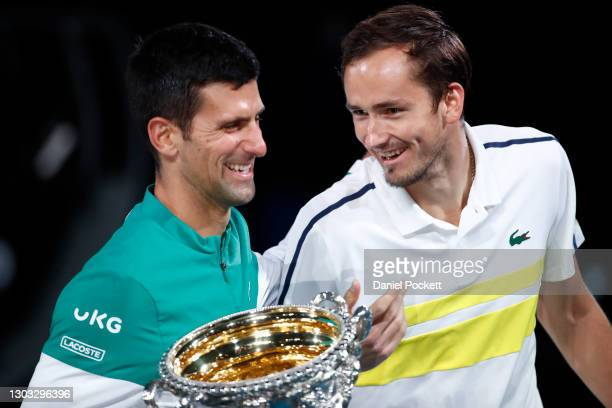 Novak Djokovic of Serbia holds the Norman Brookes Challenge Cup as he shares a joke with opponent Daniil Medvedev of Russia following their Men's...