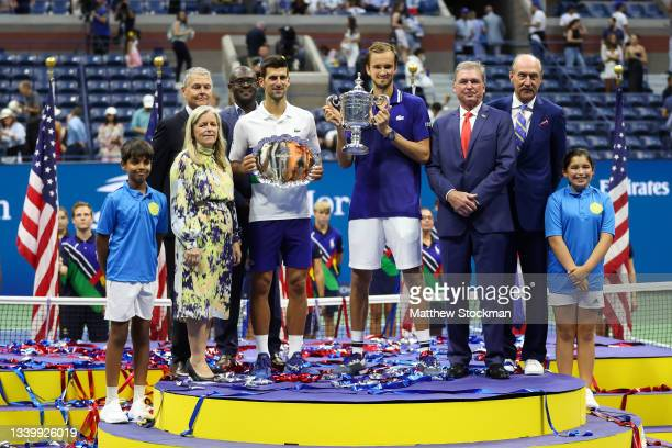 Novak Djokovic of Serbia holds the runner-up trophy alongside Daniil Medvedev of Russia who celebrates with the championship trophy after winning...