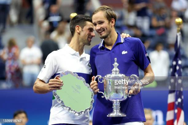 Novak Djokovic of Serbia holds the runner-up trophy and talks with Daniil Medvedev of Russia who celebrates with the championship trophy after...
