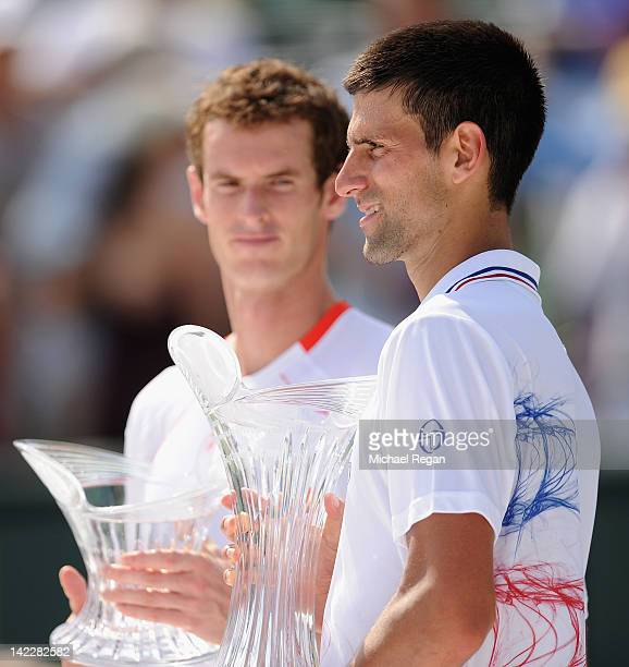 Novak Djokovic of Serbia holds the winner's trophy as Andy Murray of Great Britain looks on after the men's singles final on day 14 of the Sony...