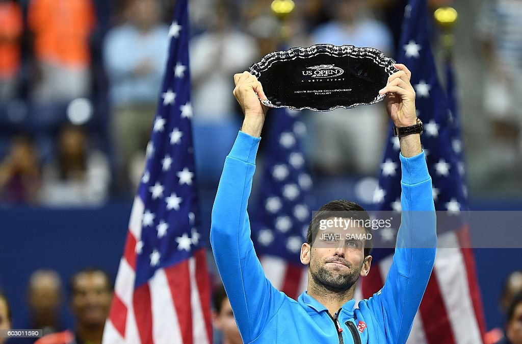TOPSHOT - Novak Djokovic of Serbia holds up his runner up trophy after during the presentation after being defeated by Stan Wawrinka of Switzerland in their 2016 US Open Men's Singles final match at the USTA Billie Jean King National Tennis Center in New York on September 11, 2016. Stan Wawrinka became the oldest US Open men's champion in 46 years when he defeated world number one Novak Djokovic to claim a third Grand Slam title on Sunday. / AFP / Jewel SAMAD