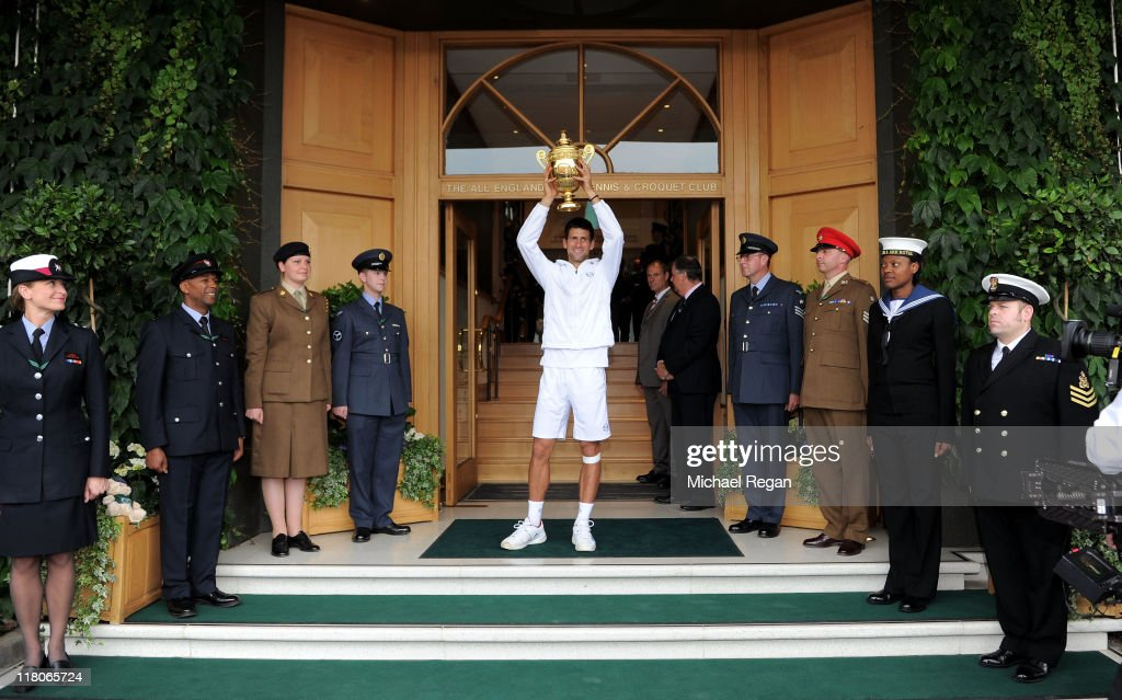 Novak Djokovic of Serbia holds up the championship trophy outside the members entrance after winning his final round Gentlemen's match against Rafael Nadal of Spain on Day Thirteen of the Wimbledon Lawn Tennis Championships at the All England Lawn Tennis and Croquet Club on July 3, 2011 in London, England.