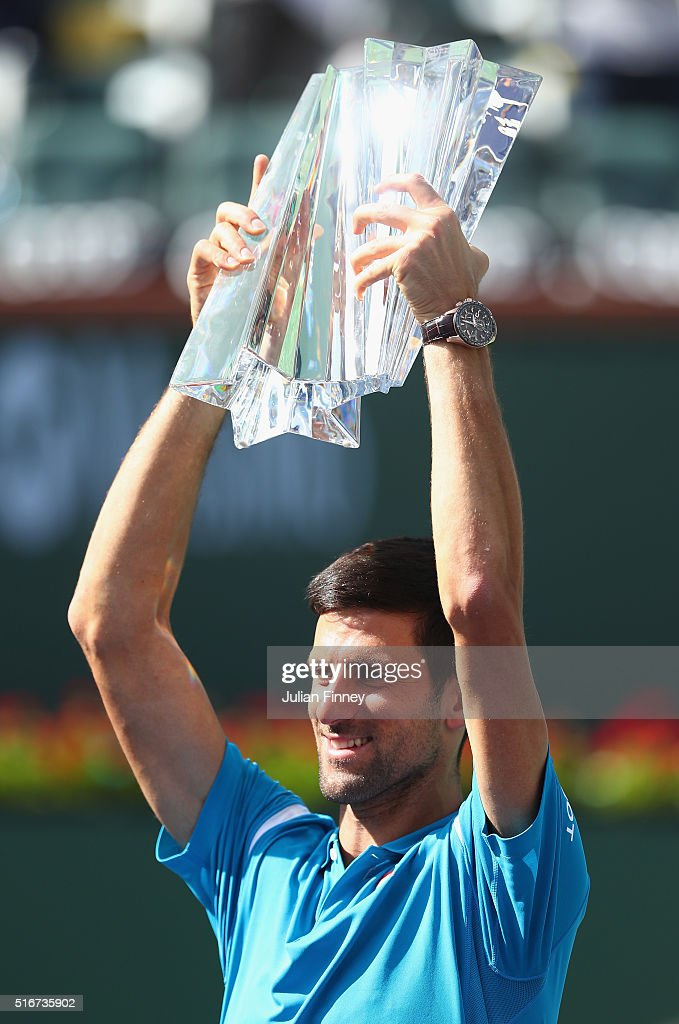 Novak Djokovic of Serbia holds up the winners trophy after his win over Milos Raonic of Canada during day fourteen of the BNP Paribas Open at Indian Wells Tennis Garden on March 20, 2016 in Indian Wells, California.
