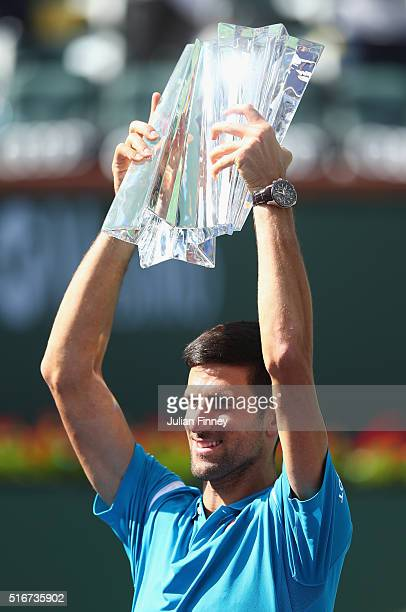 Novak Djokovic of Serbia holds up the winners trophy after his win over Milos Raonic of Canada during day fourteen of the BNP Paribas Open at Indian...