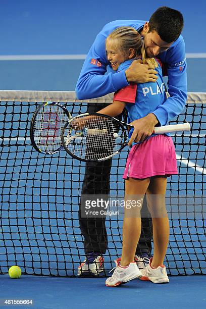Novak Djokovic of Serbia hugs Anna Bishop ANZ Hot Shots winner after a hit up on Rod Laver Arena at Melbourne Park on January 15 2015 in Melbourne...