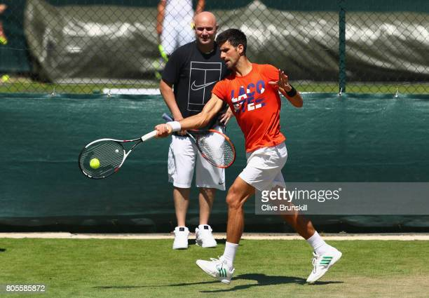 Novak Djokovic of Serbia in action watched by his coach Andre Agassi during practice ahead of the Wimbledon Lawn Tennis Championships at the All...