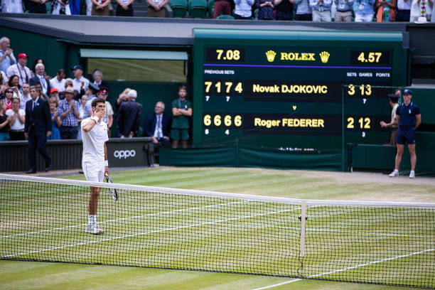 Novak Djokovic of Serbia in front of the scoreboard after defeating Roger Federer of Switzerland during the Men's Singles Final at The Wimbledon Lawn...