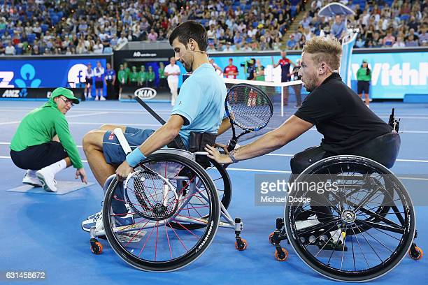 Novak Djokovic of Serbia is helped along by Australian wheelchair tennis player Dylan Alcott before playing with him during 'A Night with Novak' at...