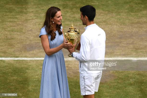 Novak Djokovic of Serbia is presented with the trophy by Catherine Duchess of Cambridge after winning his Men's Singles final against Roger Federer...