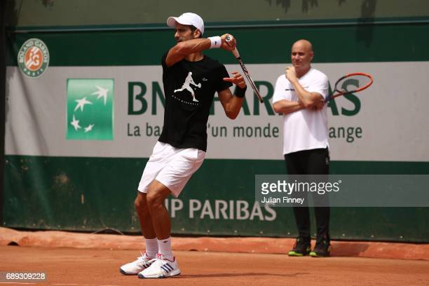 Novak Djokovic of Serbia is watched by coach Andre Agassi during practice on day one of the 2017 French Open at Roland Garros on May 28 2017 in Paris...