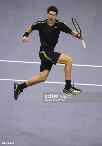Novak Djokovic of Serbia jumps into the air as he celebrates a break of serve against Nikolay Davydenko of Russia in their men's singles final at the...