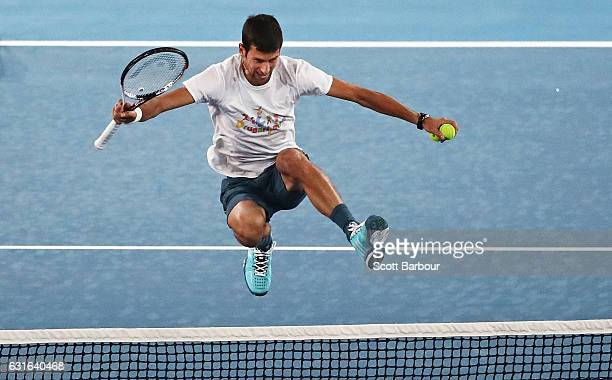 Novak Djokovic of Serbia jumps the net at the fifth annual Kids Tennis Day ahead of the 2017 Australian Open at Melbourne Park on January 14 2017 in...