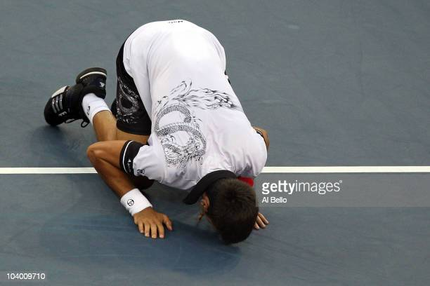 Novak Djokovic of Serbia kisses the court after defeating Roger Federer of Switzerland to win his men's singles semifinal match on day thirteen of...