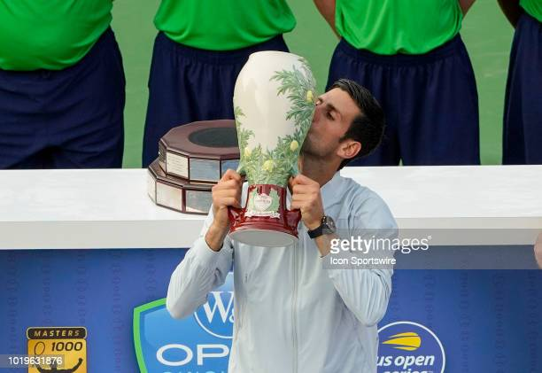 Novak Djokovic of Serbia kisses the trophy after defeating Roger Federer of Switzerland in the Western Southern Open singles final at the Lindner...