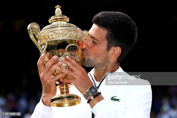 Novak Djokovic of Serbia kisses the trophy after winning his Men's Singles final against Roger Federer of Switzerland during Day thirteen of The...