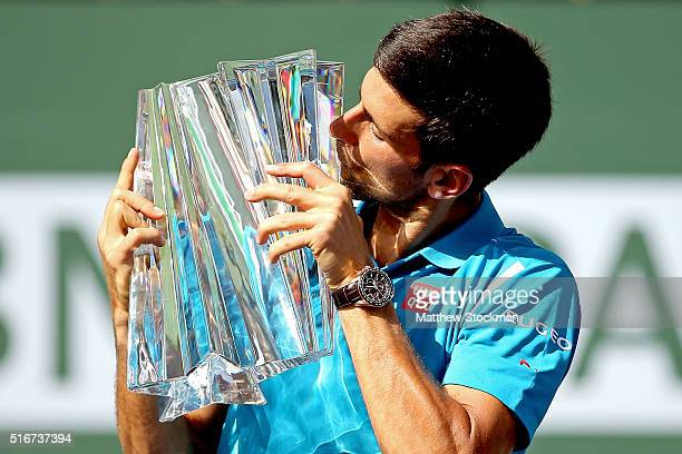 Novak Djokovic of Serbia kisses the winner's trophy after defeating Milos Raonic of Canada during the mens final of the BNP Paribas Open at the...