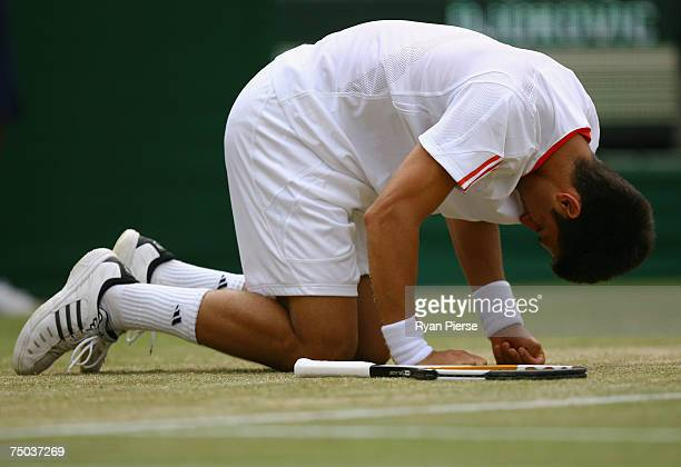 Novak Djokovic of Serbia kneels on the grass during the Men's Singles fourth round match against Lleyton Hewitt of Australia during day ten of the...