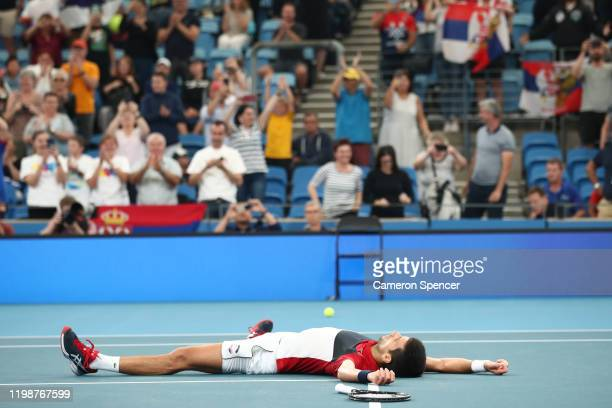 Novak Djokovic of Serbia lays on the court celebrating match point during his semifinal singles match against Daniil Medvedev of Russia on day nine...