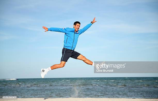 Novak Djokovic of Serbia leaps in the air on Crandon Park beach after his three set victory against Andy Murray of Great Britain in the mens final...